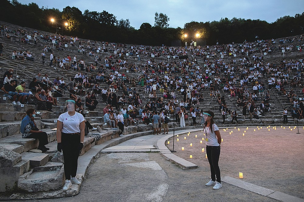 Stewards wearing surgical gloves and plastic visors stands as spectators take their seats at the ancient theater of Epidaurus, Greece, on Friday, July 17, 2020 Greek Culture Ministry allowed the ancient theaters of Epidaurus in southern Greece and Herodes Atticus in Athens to host performances under strict safety guidelines due the COVID-19 pandemic.(AP Photo/Petros Giannakouris)