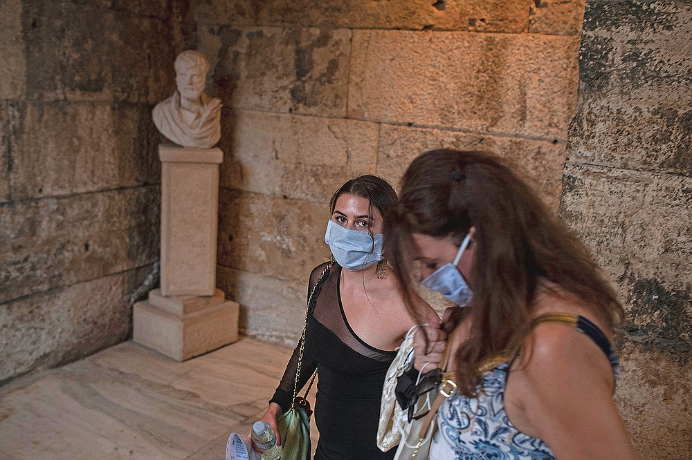 Spectators wearing protective face masks to prevent the spread of the coronavirus arrive at the Odeon of Herodes Atticus in Athens, on Wednesday, July 15, 2020. Greek Culture Ministry allowed the ancient theaters of Epidaurus in southern Greece and Herodes Atticus in Athens to host performances under strict safety guidelines due the COVID-19 pandemic.(AP Photo/Petros Giannakouris)