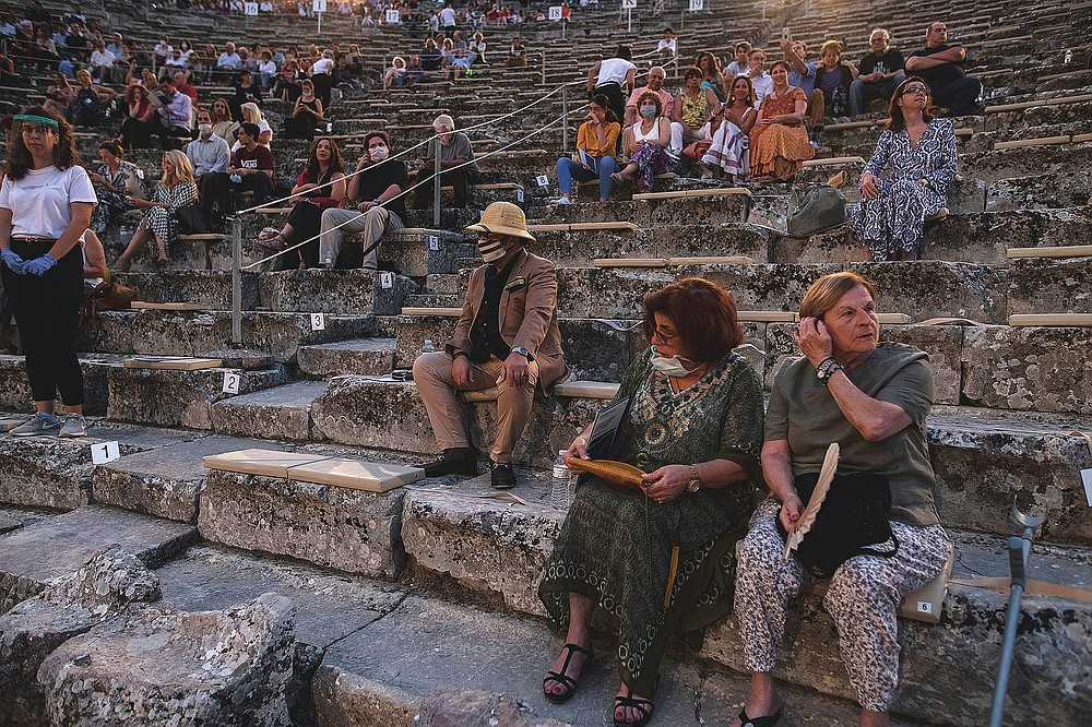 Spectators, some of them wearing protective face masks sit at the ancient theater of Epidaurus, Greece on Friday, July 17, 2020. The ancient theaters of Herodes Atticus in Athens and Epidaurus in the southern Peloponnese area have reopened for performances with strict seating limits and public health safety guidelines.(AP Photo/Petros Giannakouris)