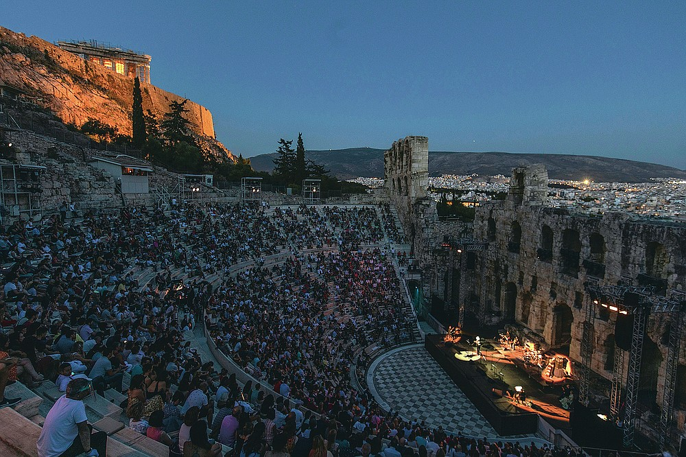 Actors and singers perform at the Odeon of Herodes Atticus in Athens, Greece, after the site was reopened for performances on Wednesday, July 15, 2020, with the ancient Parthenon temple in the background. Seating limits have been imposed at the renovated ancient stone Roman theater, underneath the Acropolis, as part of the restrictions due to the COVID-19 pandemic. Authorities allowed the venue to reopen despite recently canceling some other summer events to avoid crowding.(AP Photo/Petros Giannakouris)
