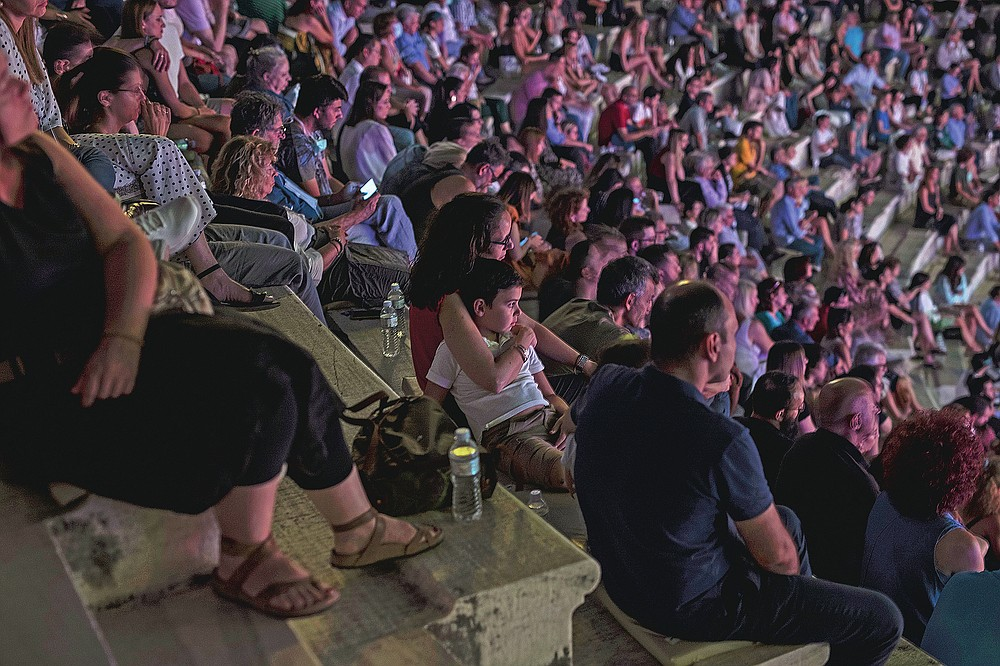 A woman hugs her child during a concert at Odeon of Herodes Atticus in Athens, on Wednesday, July 15, 2020. Greek Culture Ministry allowed the ancient theaters of Epidaurus in southern Greece and Herodes Atticus in Athens to host performances under strict safety guidelines due the COVID-19 pandemic.(AP Photo/Petros Giannakouris)
