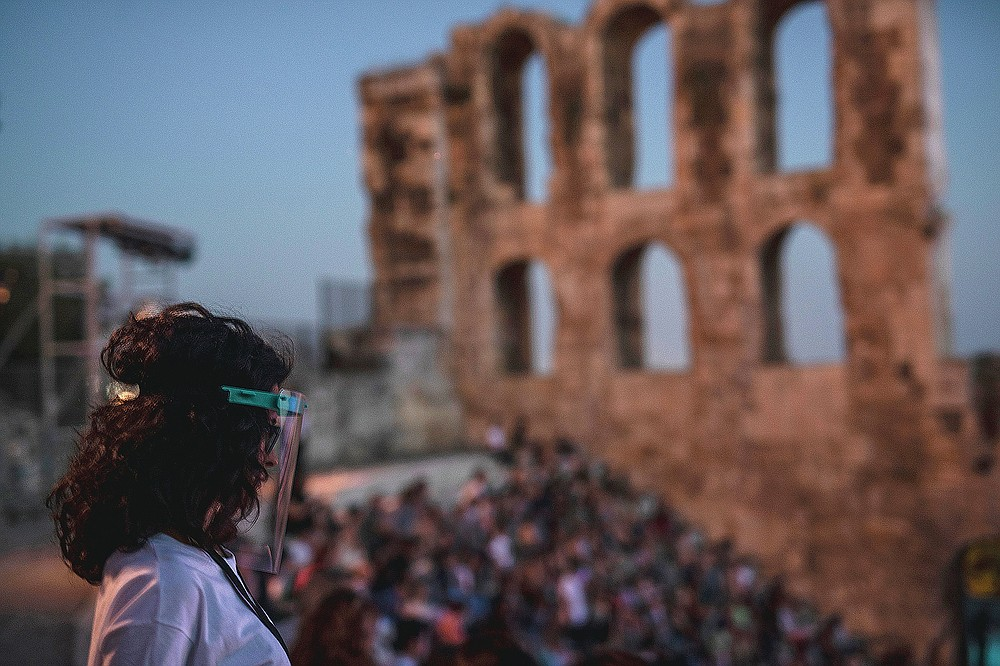 A steward wearing a plastic visor stands at the Odeon of Herodes Atticus in Athens, during a concert ,on Wednesday, July 15, 2020. Seating limits have been imposed at the renovated ancient stone Roman theater, underneath the Acropolis, as part of the restrictions due to the COVID-19 pandemic. (AP Photo/Petros Giannakouris)