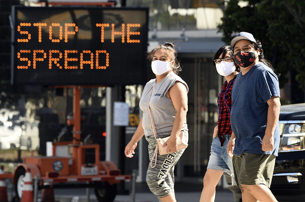 FILE - Pedestrians wear masks as they walk in front of a sign reminding the public to take steps to stop the spread of coronavirus, Thursday, July 23, 2020, in Glendale, Calif. Los Angeles County is seeing some hopeful signs amid the coronavirus surge. The county reported Wednesday that COVID-19 hospitalization and transmission rates are dropping. (AP Photo/Chris Pizzello, File)