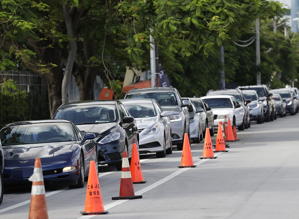 A line of cars wait at the entrance to a kosher food drive-thru distribution site, Wednesday, July 29, 2020, at the Greater Miami Jewish Federation building in Miami. (AP Photo/Wilfredo Lee)