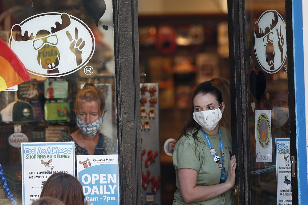 A worker at a gift shop regulated the number of customers allowed in the store due to the coronavirus pandemic, Thursday, July 30, 2020, in Portland, Maine.   State officials reported more cases of COVID-19. (AP Photo/Robert F. Bukaty)