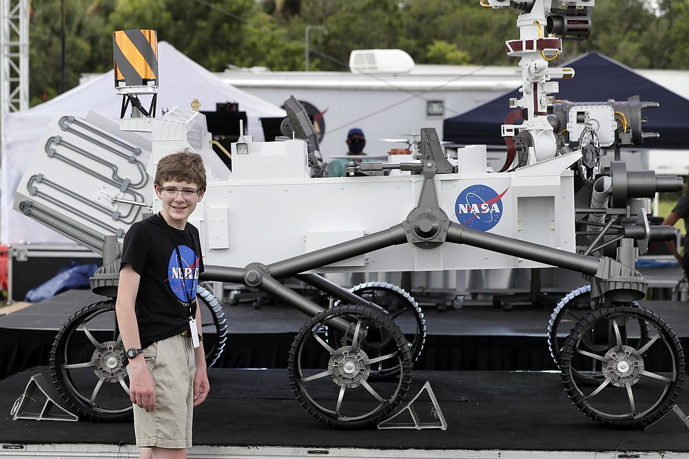 """Alexander Mather, of Burke, Va. stands next to a model of the Mars 2020 rover he named in a contest during a news conference at the Kennedy Space Center Tuesday, July 28, 2020, in Cape Canaveral, Fla. Mather, submitted the winning entry in NASA's """"Name the Rover"""" essay contest, making the case to name the Mars 2020 rover """"Perseverance."""" (AP Photo/John Raoux)"""