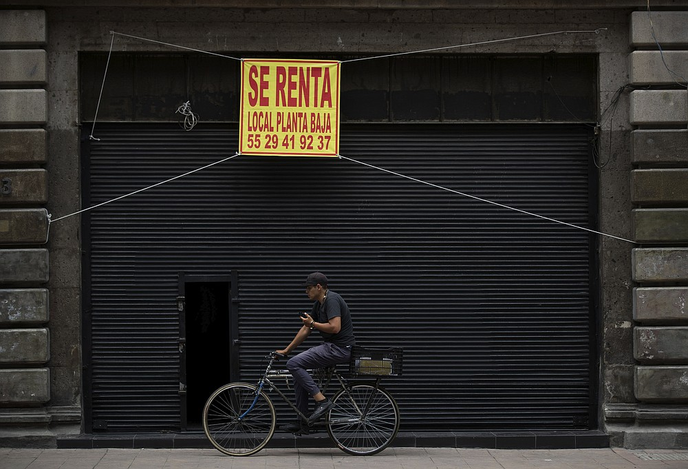 A man rides his bike past a shuttered local that is being offered for rent in downtown Mexico City, Tuesday, July 28, 2020. With the country facing a deep economic recession, Mexican President Andres Manuel Lopez Obrador has pushed to reopen the economy quickly even as COVID-19 infections and deaths continue to rise. (AP Photo/Fernando Llano)