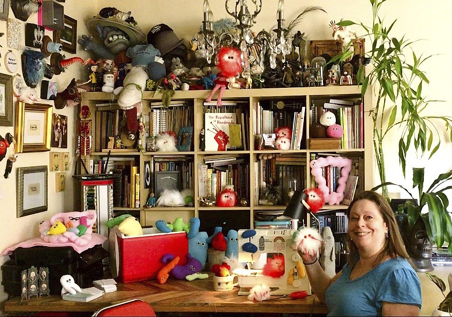 """This July 25, 2020 photo shows Amy Micallef posing with her craft creations at her home. While Broadway stages remain dark due to the pandemic, Broadway workers are concentrating on side hustles. Micallef, a Broadway seamstress who has worked in the wardrobe departments of """"Hamilton,"""" """"Waitress"""" and """"Frozen,"""" makes gleeful representations of COVID-19 for sale, complete with a pair of eyes and faux fur. (Amy Micallef via AP)"""