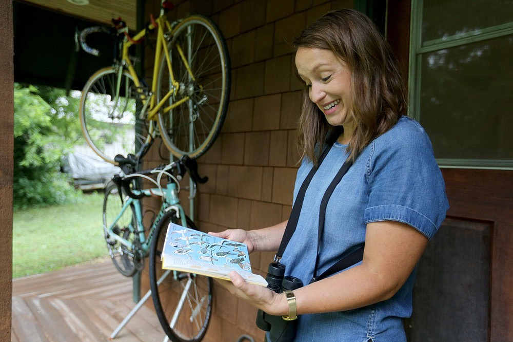 Meredith Bergstrom looks at a favorite bird book Thursday, July 9, 2020, in the backyard of her Siloam Springs home. With the pandemic Bergstrom has had the opportunity to spend more time pursuing her bird watching hobby. Check out nwaonline.com/200723Daily/ and nwadg.com/photos for a photo gallery. (NWA Democrat-Gazette/David Gottschalk)