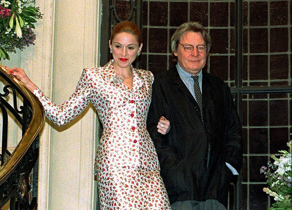 "FILE - Actress-singer Madonna arrives for a news conference about the musical film ""Evita"" with British director Alan Parker in Buenos Aires on Feb.6, 1996. Parker, whose movies included ""Bugsy Malone,"" ""Midnight Express"" and ""Evita,"" has died at the age of 76. A statement from the director's family says Parker died Friday in London after a long illness. (AP Photo/Daniel Muzio, File)"