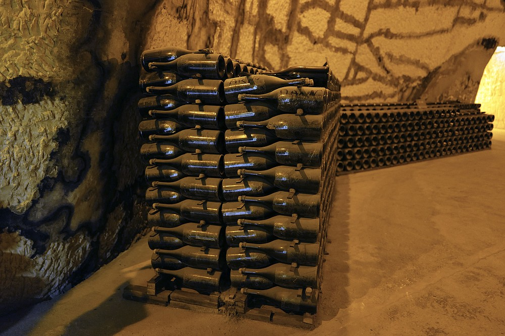 Champagne bottles piled in the cave of the Vranken-Pommery Monopole in Reims, the Champagne region, east of Paris, Tuesday, July 28, 2020. Producers in France's eastern Champagne region, headquarters of the global industry, say they've lost about 1.7 billion euros ($2 billion) in sales this year, as turnover fell by a third —  a hammering unmatched in living memory, and worse than the Great Depression. (AP Photo/Francois Mori)