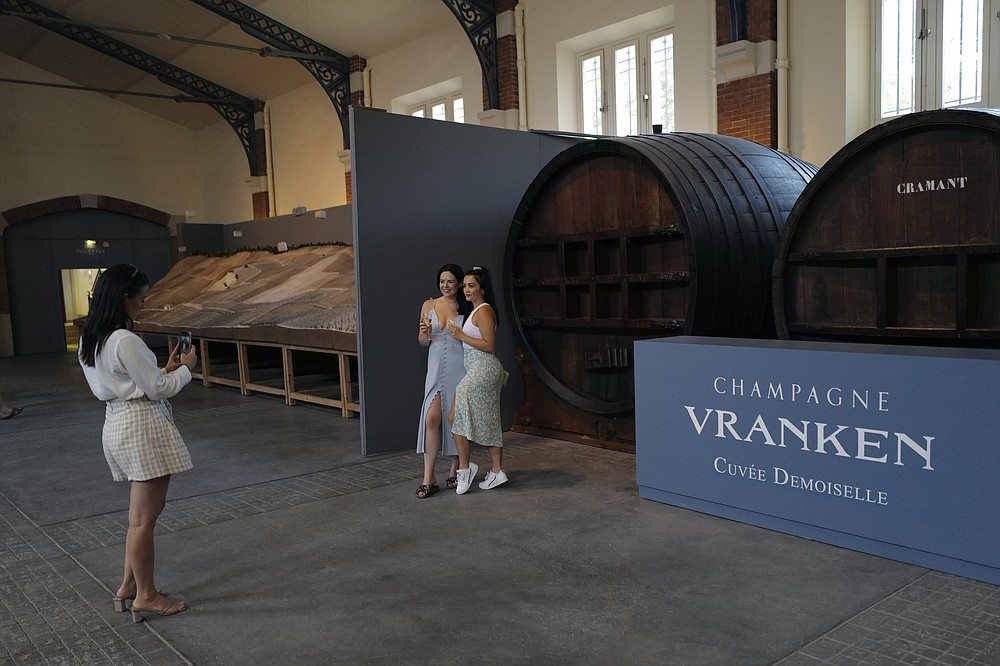 Visitors from London, take photos with a glass of Champagne as they visit the Vranken-Pommery Monopole in Reims, the Champagne region, east of Paris, Tuesday, July 28, 2020. Producers in France's eastern Champagne region, headquarters of the global industry, say they've lost about 1.7 billion euros ($2 billion) in sales this year, as turnover fell by a third —  a hammering unmatched in living memory, and worse than the Great Depression. (AP Photo/Francois Mori)