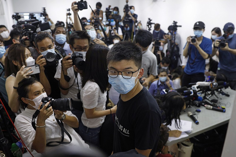 Hong Kong pro-democracy activist Joshua Wong, center, attends a press conference in Hong Kong, Friday, July 31, 2020. At least 12 Hong Kong pro-democracy nominees including prominent activist Joshua Wong were disqualified for September legislative elections, with authorities saying Thursday they failed to uphold the city's mini-constitution and pledge allegiance to Hong Kong and Beijing. (AP Photo/Kin Cheung)
