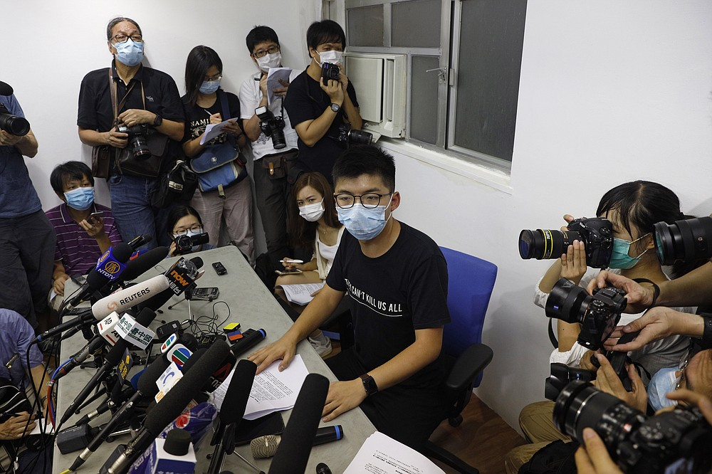 Hong Kong pro-democracy activist Joshua Wong, center, attends a press conference in Hong Kong, Friday, July 31, 2020. On Thursday, 12 pro-democracy candidates including prominent pro-democracy activist Joshua Wong were disqualified from running in the legislative elections, as they were deemed to not comply with the Basic Law or pledge allegiance to the city and Beijing.(AP Photo/Kin Cheung)