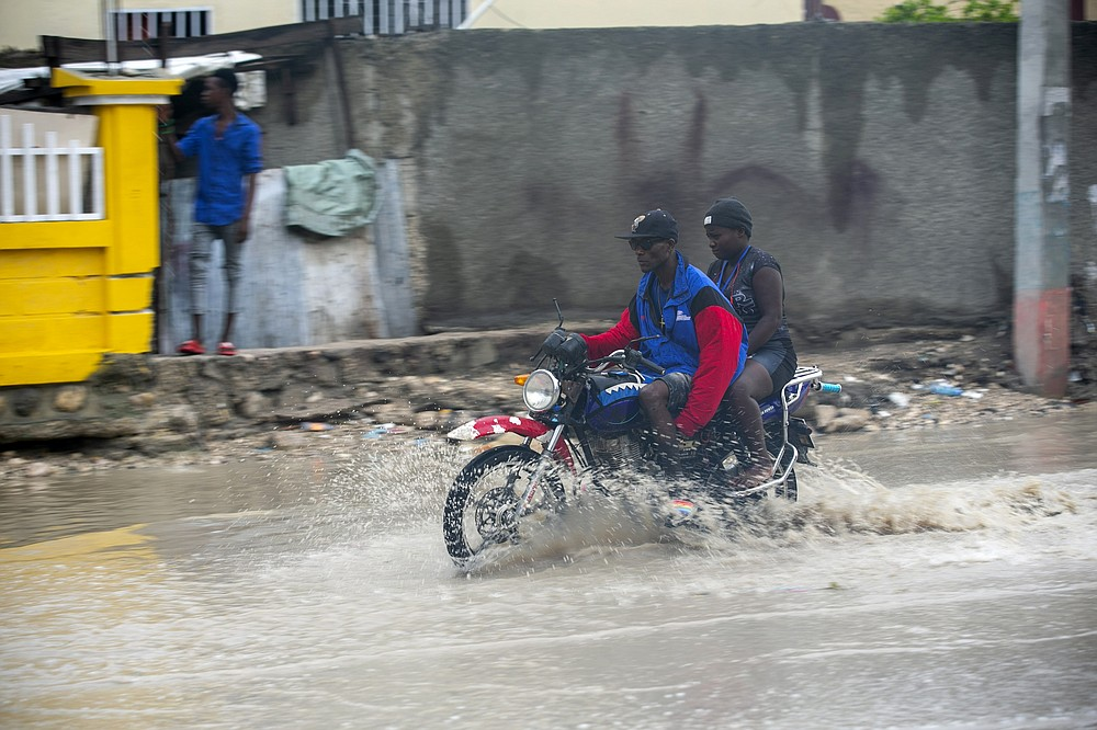 A moto-taxi driver moves through a street flooded by rain brought by the outer bands of Hurricane Isaias, in the Tabarre district of Port-au-Prince, Haiti, early Friday, July 31, 2020. Isaias kept on a path early Friday toward the U.S. East Coast as it approached the Bahamas. (AP Photo/Dieu Nalio Chery)
