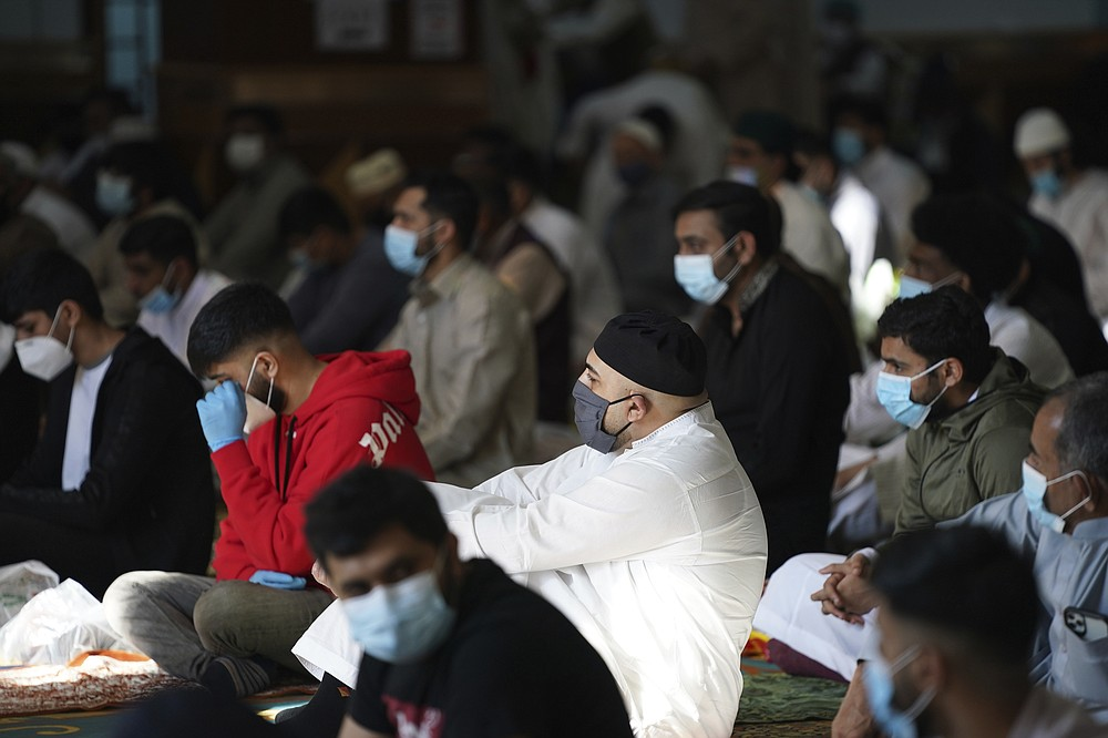 Men wearing face masks sit inside Manchester Central Mosque, in Manchester, northern England, after having their temperatures checked at the entrance to try stop the spread of coronavirus, as Muslims worldwide mark the start of the Eid al-Adha holiday, Friday, July 31, 2020. The British government on Thursday night announced new rules on gatherings in some parts of Northern England, including Manchester, that people there should not mix with other households in private homes or gardens in response to an increase trend in the number of cases of coronavirus cases per 100,000 people. (AP Photo/Jon Super)