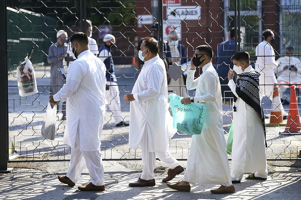 People wearing face masks arrive before having their temperatures checked to try stop the spread of coronavirus, before being allowed to go into Manchester Central Mosque, in Manchester, northern England, as Muslims worldwide mark the start of the Eid al-Adha holiday, Friday, July 31, 2020. The British government on Thursday night announced new rules on gatherings in some parts of Northern England, including Manchester, that people there should not mix with other households in private homes or gardens in response to an increase trend in the number of cases of coronavirus cases per 100,000 people. (AP Photo/Jon Super)