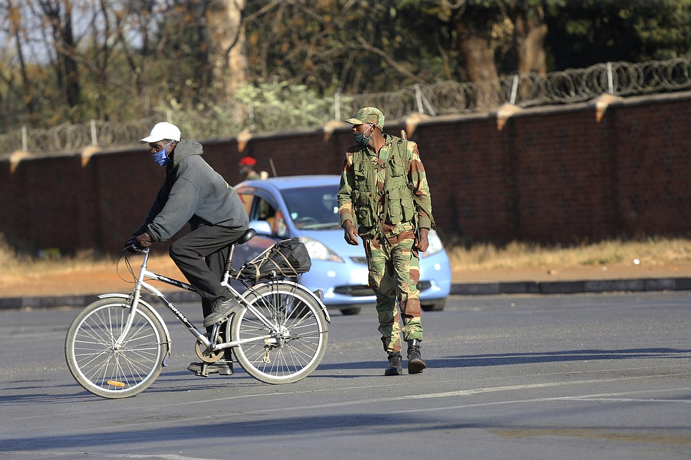 An armed soldier is seen on a street in Harare, Friday, July, 31, 2020. Zimbabwe's capital, Harare, was deserted Friday, as security agents vigorously enforced the country's lockdown amidst planned protests. Police and soldiers manned checkpoints and ordered people seeking to get into the city for work and other chores to return home. (AP Photo/Tsvangirayi Mukwazhi)