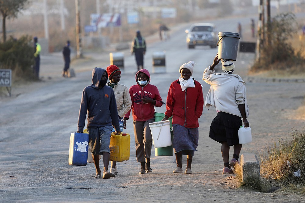 People carry buckets to fetch water past a police checkpoint in Harare, Friday, July, 31, 2020. Zimbabwe's capital, Harare, was deserted Friday, as security agents vigorously enforced the country's lockdown amidst planned protests. Police and soldiers manned checkpoints and ordered people seeking to get into the city for work and other chores to return home. (AP Photo/Tsvangirayi Mukwazhi)