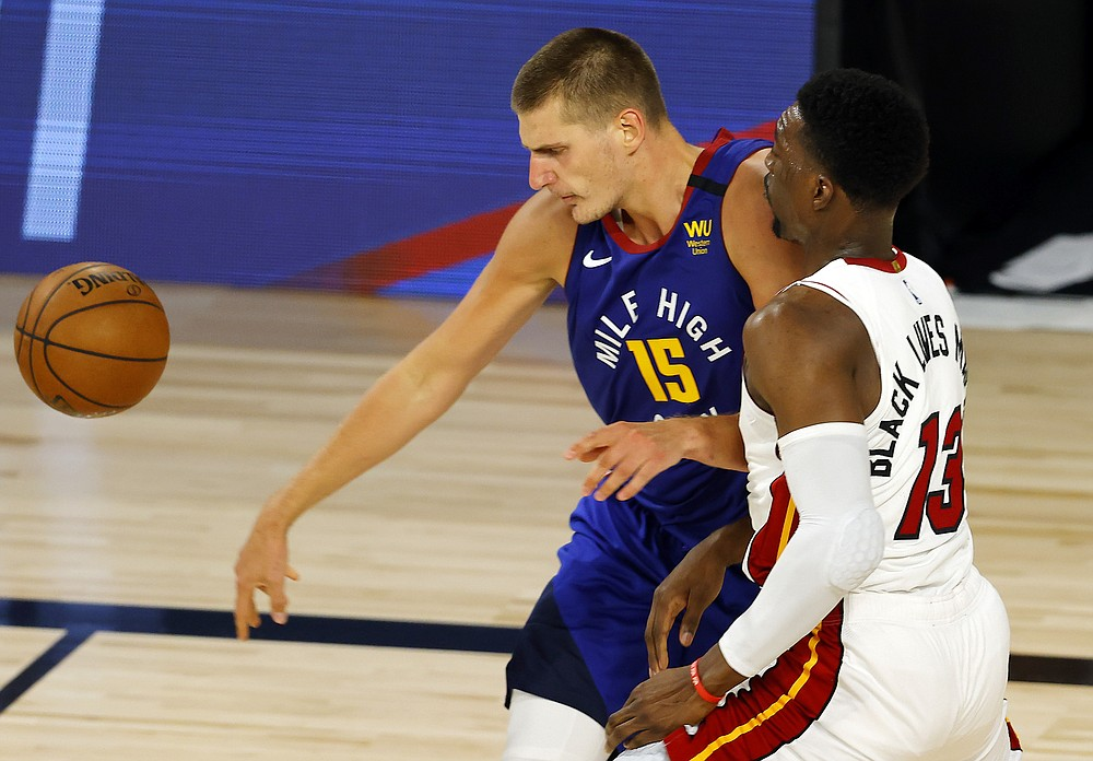 Denver Nuggets' Nikola Jokic loses control of the ball against Miami Heat's Bam Adebayo during an NBA basketball game, Saturday, Aug. 1, 2020, in Lake Buena Vista, Fla. (Kevin C. Cox/Pool Photo via AP)