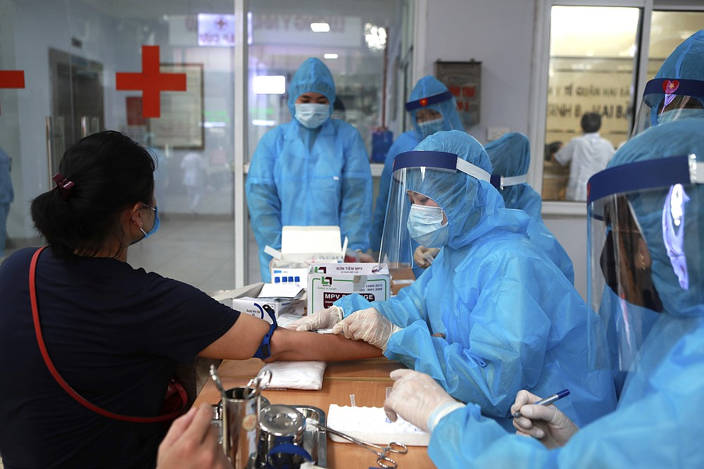 A health worker draws blood for COVID-19 test in Hanoi, Vietnam on Friday, July 31, 2020. Vietnamese state media on Friday reported the country's first-ever death of a person with the coronavirus as it struggles with a renewed outbreak after 99 days without any cases. (AP Photo/Hau Dinh)