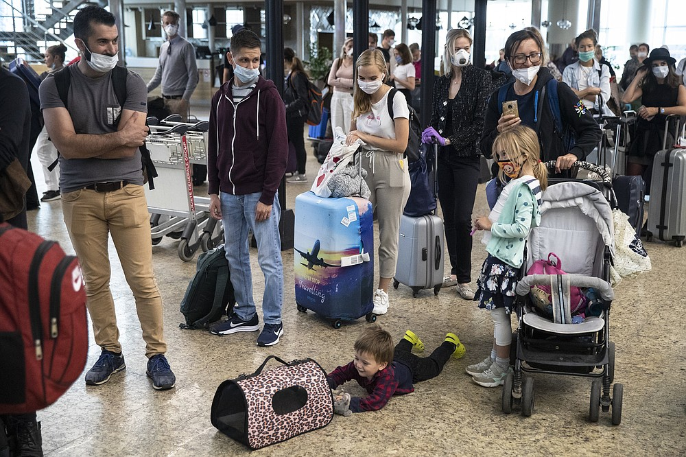 A child plays with a pet as people wait in line to check-in at Sheremetyevo international airport, outside Moscow, Russia, Saturday, Aug. 1, 2020. Russia restarts international flights to Britain, Turkey and Tanzania on Aug. 1 more than four months after closing its borders due to the coronavirus pandemic. (AP Photo/Pavel Golovkin)