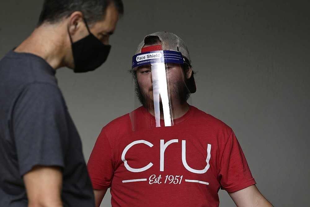 Volunteer and student Nathan Hsieh wears a face shield as he assists college students who begin moving in for the fall semester at N.C. State University in Raleigh, N.C., Friday, July 31, 2020. The first wave of college students returning to their dorms aren't finding the typical mobs of students and parents. At N.C. State, the return of students was staggered over 10 days and students were greeted Friday by socially distant volunteers donning masks and face shields. (AP Photo/Gerry Broome)