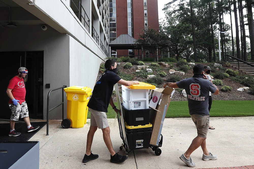 College students begin moving in for the fall semester at N.C. State University in Raleigh, N.C., Friday, July 31, 2020. The first wave of college students returning to their dorms aren't finding the typical mobs of students and parents. At N.C. State, the return of students was staggered over 10 days and students were greeted Friday by socially distant volunteers donning masks and face shields. (AP Photo/Gerry Broome)