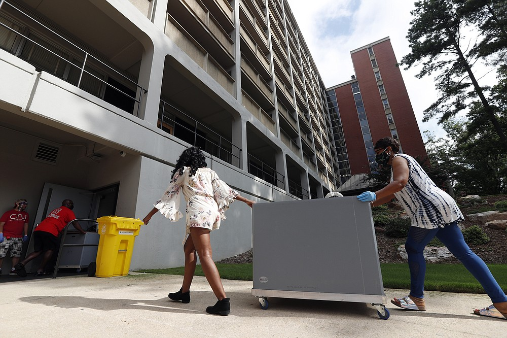 College students begin moving in for the fall semester at N.C. State University in Raleigh, N.C., Friday, July 31, 2020. The first wave of college students returning to their dorms aren't finding the typical mobs of students and parents. At N.C. State, the return of students was staggered over 10 days and students were greeted Friday by socially distant volunteers donning masks and face shields. . (AP Photo/Gerry Broome)