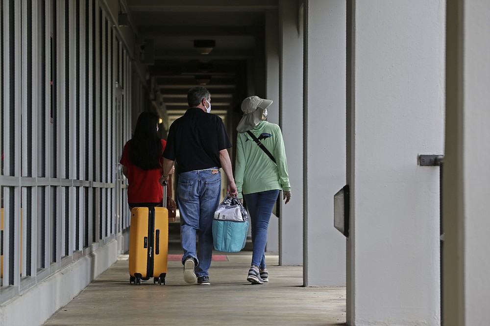 A family walks down a corridor at Lee Hall as college students begin moving in for the fall semester at N.C. State University in Raleigh, N.C., Friday, July 31, 2020. The first wave of college students returning to their dorms aren't finding the typical mobs of students and parents. At N.C. State, the return of students was staggered over 10 days and students were greeted Friday by socially distant volunteers donning masks and face shields. (AP Photo/Gerry Broome)