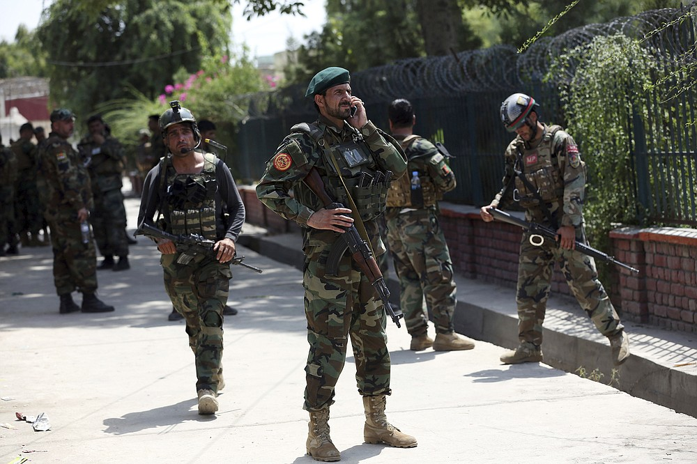 Afghan security personnel gather near a prison after an attack in the city of Jalalabad, east of Kabul, Afghanistan, Monday, Aug. 3, 2020. An Islamic State group attack on the prison in eastern Afghanistan holding hundreds of its members raged on Monday after killing people in fighting overnight, a local official said. (AP Photo/Rahmat Gul)