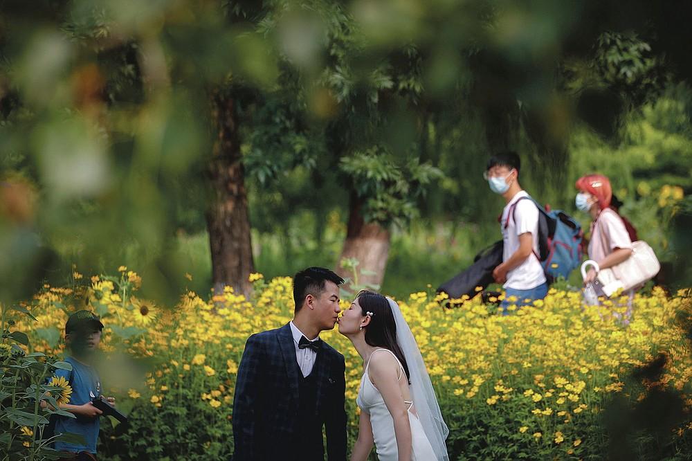 DOSSIER - Des personnes portant des masques faciaux passent devant de jeunes mariés qui s'embrassent alors qu'ils posent pour des photos de mariage au parc forestier olympique de Pékin le 2 juillet 2020. Maintenant que les mariages ont lentement augmenté sous un patchwork de restrictions toujours changeantes, les histoires d'horreur des vendeurs sont Beaucoup sont désespérés de travailler après que le coronavirus a brusquement mis fin à leurs revenus et se sentent obligés de mettre leurs masques, de saisir leurs caméras et d'espérer le meilleur. (Photo AP / Andy Wong)
