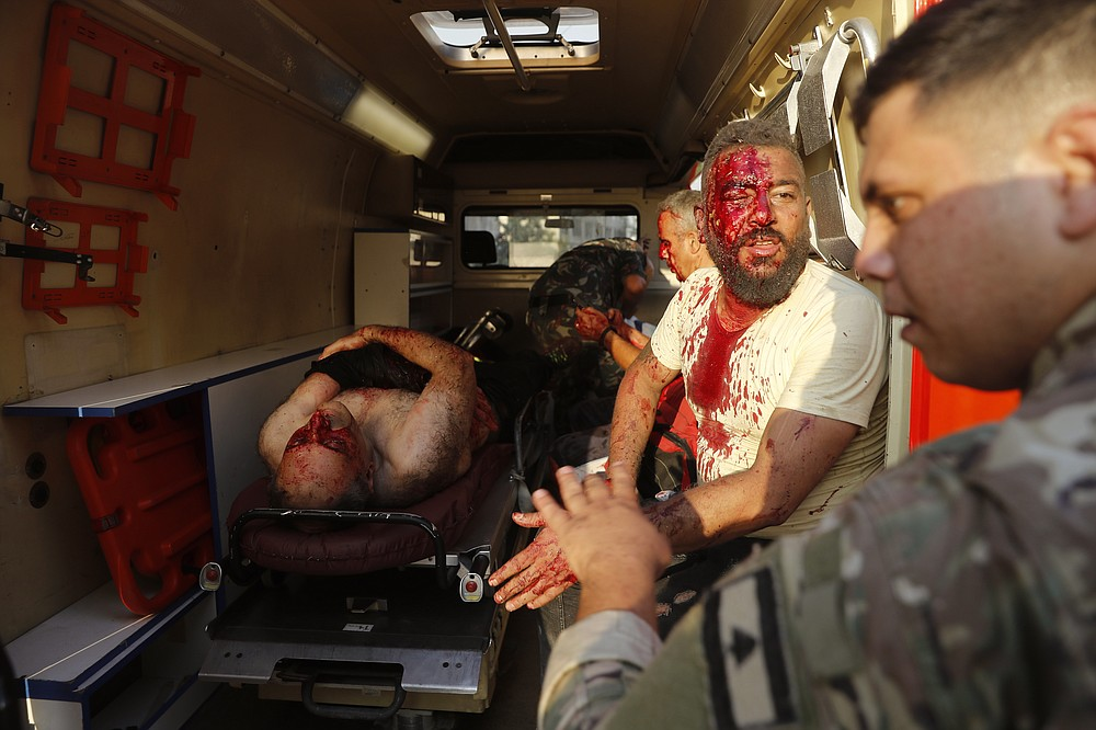 A Lebanese soldier, right, checks injured men who sit inside an umbulance at the explosion scene that hit the seaport of Beirut, Lebanon, Tuesday, Aug. 4, 2020. Massive explosions rocked downtown Beirut on Tuesday, flattening much of the port, damaging buildings and blowing out windows and doors as a giant mushroom cloud rose above the capital.  (AP Photo/Hussein Malla)