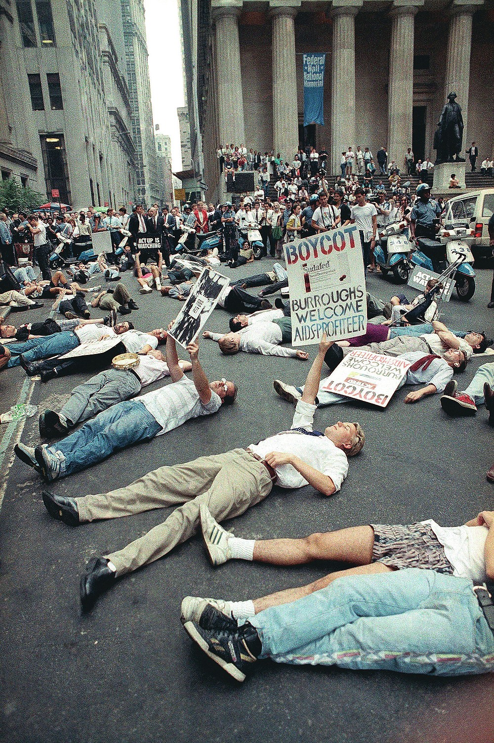 """FILE - In this Thursday, Sept. 14, 1989 file photo, protestors lie on the street in front of the New York Stock Exchange in a demonstration against the high cost of the AIDS treatment drug AZT. The protest was organized by the gay rights activist group ACT UP. In response to protests, the FDA agreed to speed testing and approval of new therapies — a key step in curbing the high death toll from AIDS. Activist Larry Kramer, who died in May, said the protesters' sense of rage made a difference. """"Until you have anger and fear, you don't have any kind of an activist movement,"""" he told Metro Weekly, a Washington-based LGBT publication, in 2011. (AP Photo/Tim Clary, File)"""