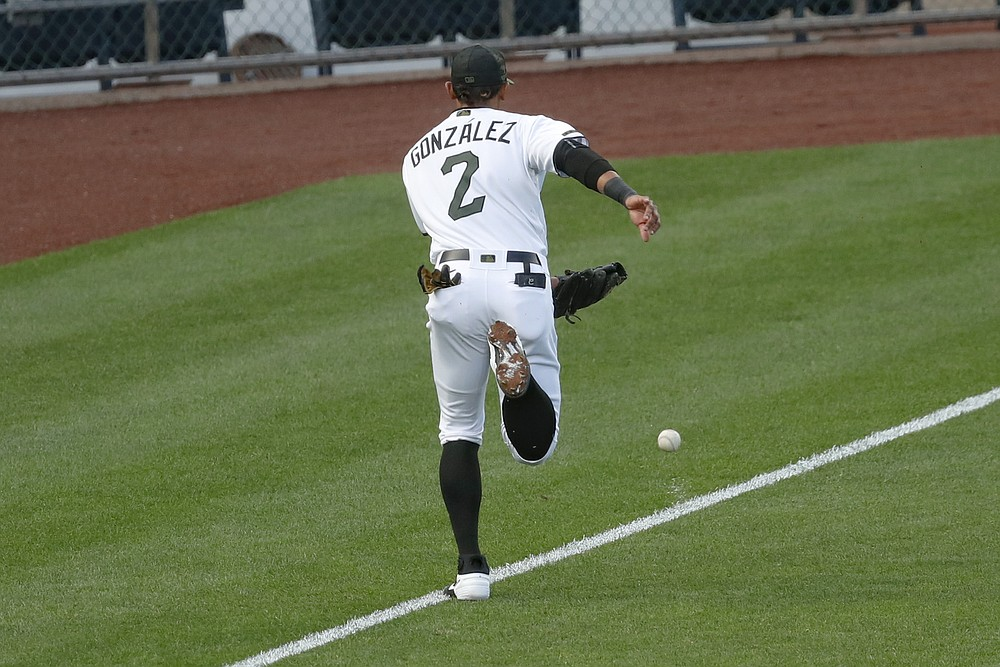 The ball kicks up some chalk as Pittsburgh Pirates third baseman Erik Gonzalez chases after a fly ball by Minnesota Twins' Marwin Gonzalez in the second inning of a baseball game, Wednesday, Aug. 5, 2020, in Pittsburgh. The call was originally a foul ball but upon review the ball was ruled fair and Jake Cave scored from second. (AP Photo/Keith Srakocic)