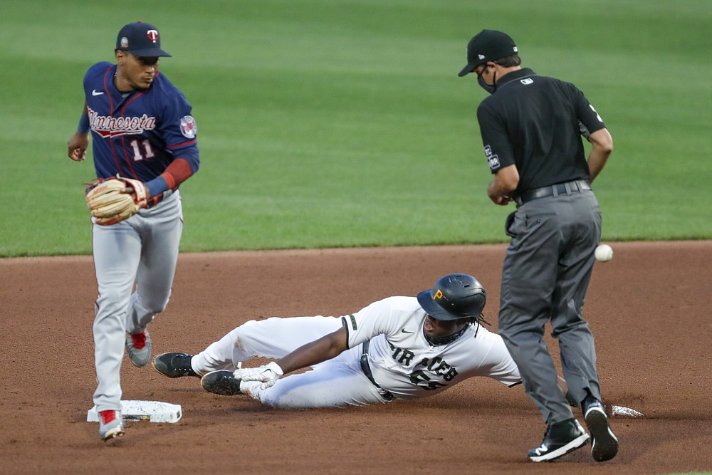 Pittsburgh Pirates' Josh Bell, center, slides into second with a double as the throw gets by Minnesota Twins shortstop Jorge Polanco (11) in the fourth inning of a baseball game, Wednesday, Aug. 5, 2020, in Pittsburgh. Second base umpire John Tumpane, right, watches the play. (AP Photo/Keith Srakocic)