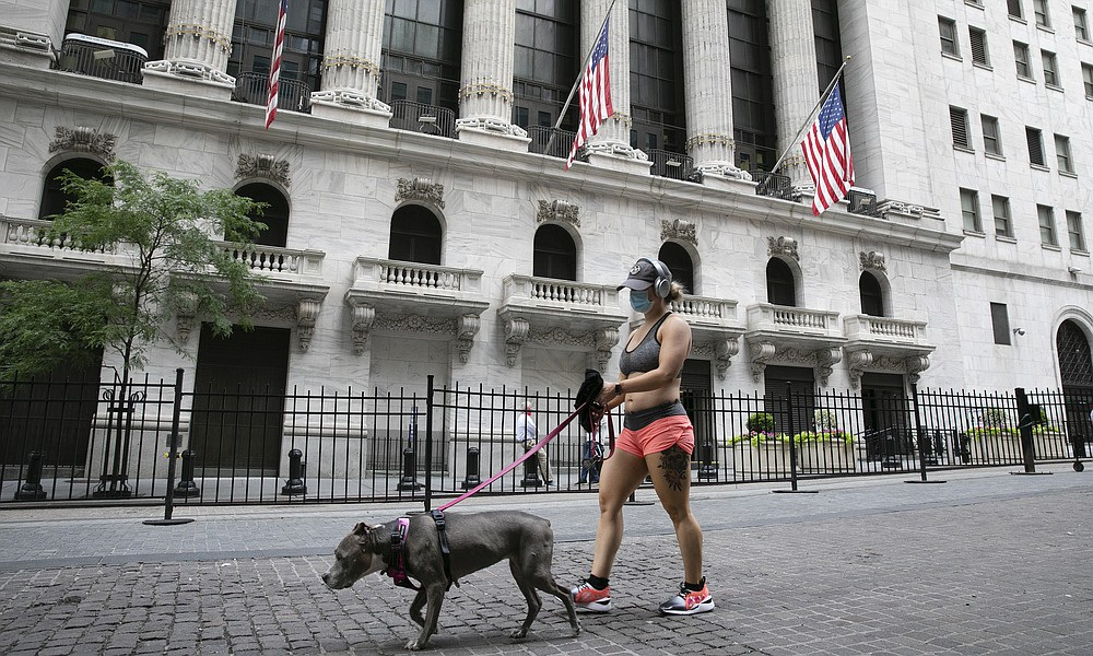 FILE - A woman wearing a mask walks her dog past the New York Stock Exchange, Tuesday, June 30, 2020.  Stocks are drifting in early trading on Wall Street Thursday, Aug. 6,  after a report suggested that the number of layoffs across the country is slowing, though it remains incredibly high. (AP Photo/Mark Lennihan)