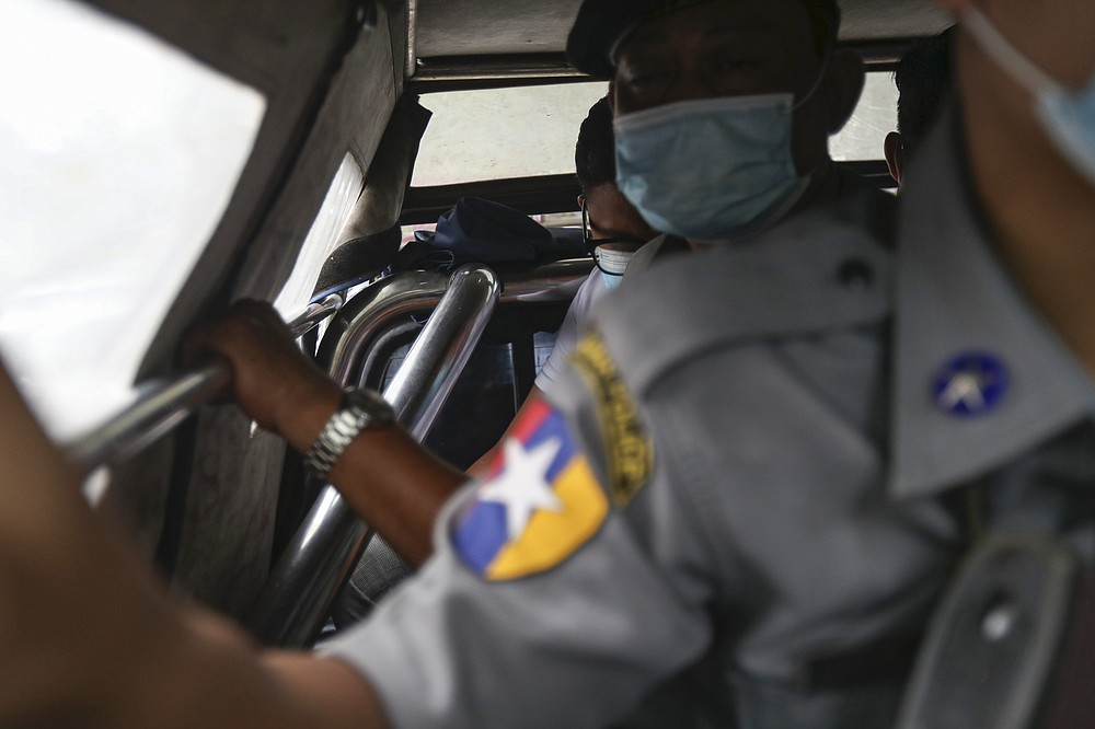 Canadian pastor David Lah, rear,  is escorted by police to a township court for a hearing Thursday, Aug. 6, 2020, in Yangon, Myanmar. The court have sentenced Lah to three months imprisonment after finding him guilty of violating a law intended to combat the spread of the coronavirus. (AP Photo/Thein Zaw)