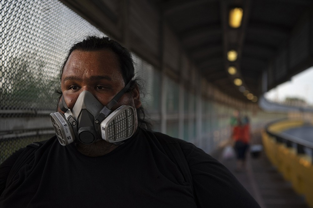A man wearing a mask walks toward Mexico. MUST CREDIT: Bloomberg photo by Callaghan O'Hare