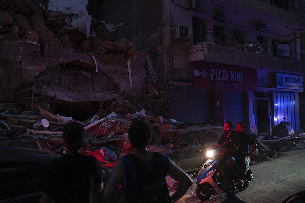 People ride past damaged buildings at a neighborhood without electricity near the scene of Tuesday's explosion that hit the seaport of Beirut, Lebanon, Friday, Aug. 7, 2020. Rescue teams were still searching the rubble of Beirut's port for bodies on Friday, nearly three days after a massive explosion sent a wave of destruction through Lebanon's capital, killing over a hundred people and wounding thousands. (AP Photo/Felipe Dana)