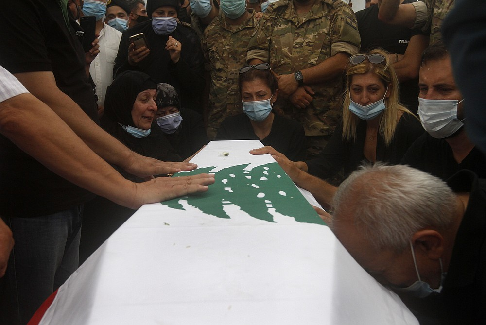 Relatives of Lebanese army lieutenant Ayman Noureddine, who was killed by Tuesday's explosion that hit the seaport of Beirut, mourn over his coffin during his funeral procession, in Numeiriyeh village, south Lebanon, Friday, Aug. 7, 2020. Rescue teams were still searching the rubble of Beirut's port for bodies on Friday, nearly three days after a massive explosion sent a wave of destruction through Lebanon's capital.  (AP Photo/Mohammed Zaatari)
