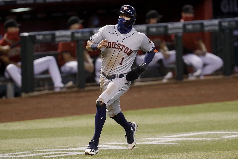 Houston Astros' Carlos Correa (1) scores on a base hit by teammate Abraham Toro during the second inning of a baseball game against the Arizona Diamondbacks Wednesday, Aug. 5, 2020, in Phoenix. (AP Photo/Matt York)
