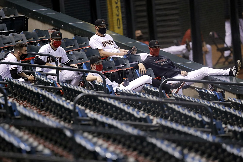Arizona Diamondbacks players sit in the stands during the first inning of a baseball game against the Houston Astros Thursday, Aug. 6, 2020, in Phoenix. (AP Photo/Matt York)