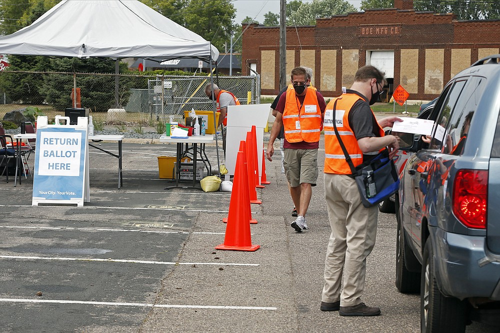 An election official inspects a ballot from a driver dropping it off Friday, Aug. 7, 2020, at an election drive-through in a parking lot at the Minneapolis Election and Voters Services headquarters in Minneapolis. Minnesota's primary election is Tuesday, Aug. 11. (AP Photo/Jim Mone)