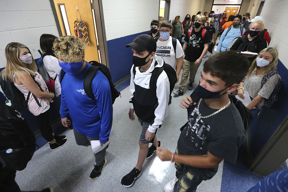 FILE - In this Aug. 6, 2020, file photo, Guntown Middle School eighth graders walk the halls to their next class as others wait in their assigned spots against the wall before moving into their next class during the first day back to school for the Lee County District in Guntown, Miss. As schools reopen around the country, their ability to quickly identify and contain coronavirus outbreaks before they get out of hand is about to be put to the test. (Adam Robison/The Northeast Mississippi Daily Journal via AP, File)