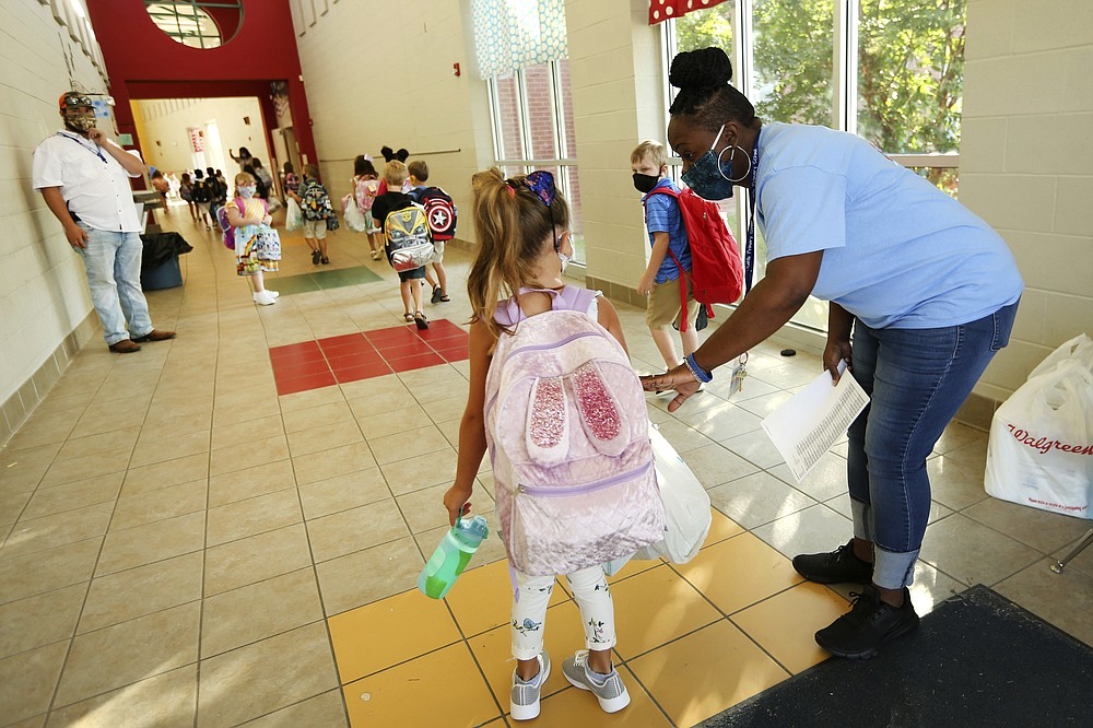 FILE - In this Aug. 6, 2020, file photo, Tannissa Jefferies, a physical education teacher at Saltillo Primary School, helps students arriving on their first day get to their proper hallway as they enter from the carpool line in Saltillo, Miss. As schools reopen around the country, their ability to quickly identify and contain coronavirus outbreaks before they get out of hand is about to be put to the test. (Adam Robison/The Northeast Mississippi Daily Journal via AP, File)