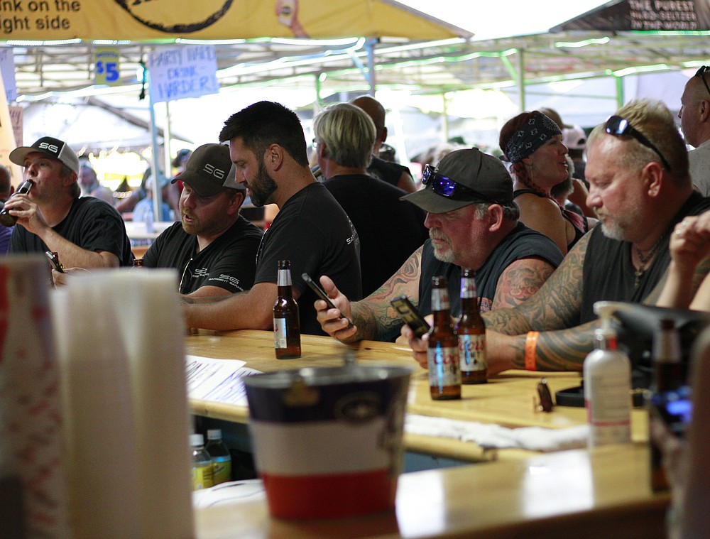 People crowded around bars in Sturgis, S.D., on Friday, Aug. 7, 2020 during the 80th anniversary of the Sturgis Motorcyle Rally. (AP Photo/Stephen Groves)