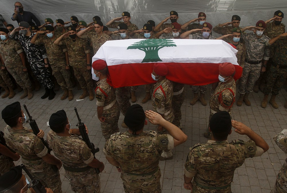 Lebanese army soldiers carry the coffin of lieutenant Ayman Noureddine, who was killed by Tuesday's explosion that hit the seaport of Beirut, during his funeral procession, in Numeiriyeh village, south Lebanon, Friday, Aug. 7, 2020. Rescue teams were still searching the rubble of Beirut's port for bodies on Friday, nearly three days after a massive explosion sent a wave of destruction through Lebanon's capital.  (AP Photo/Mohammed Zaatari)