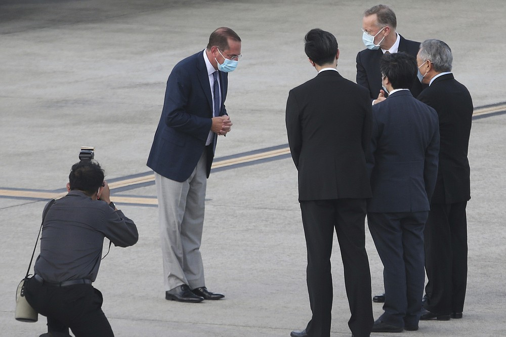 U.S. Health and Human Services Secretary Alex Azar, second left, greets Taiwanese officers as he arrives at Taipei Songshan Airport in Taipei, Taiwan, Sunday, Aug. 9, 2020. Azar arrived in Taiwan on Sunday in the highest-level visit by an American Cabinet official since the break in formal diplomatic relations between Washington and Taipei in 1979. (AP Photo/Chiang Ying-ying)