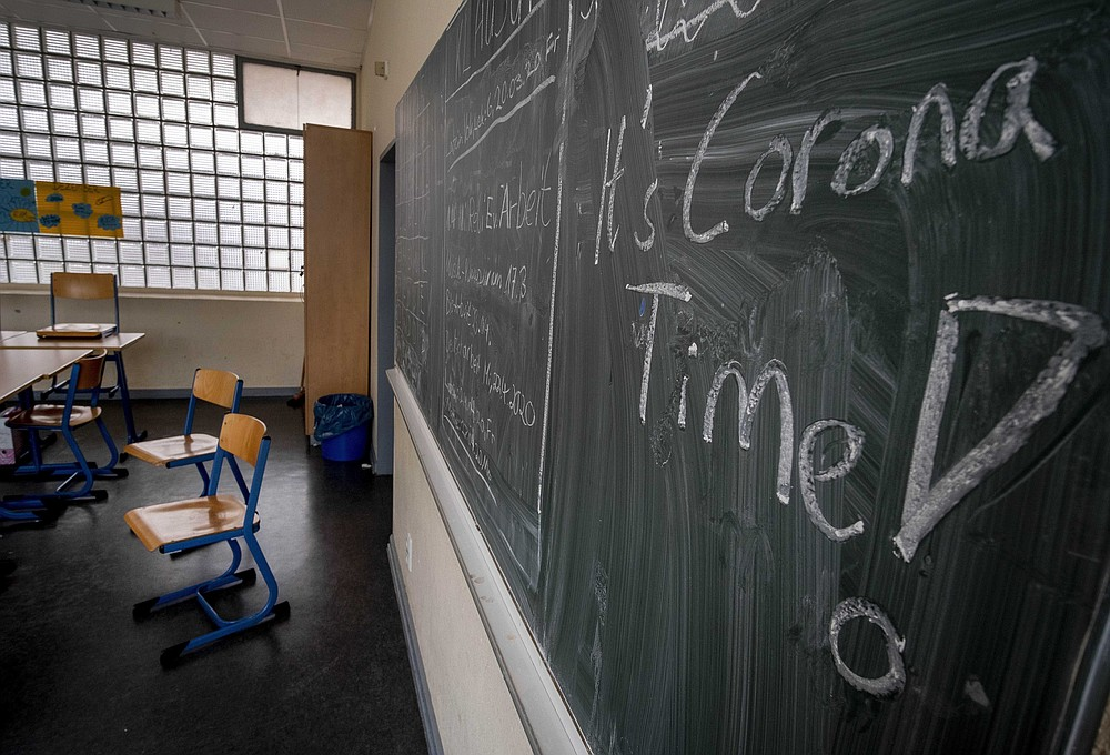 "FILE -- In this Friday, March 13, 2020 photo a slogan on a chalkboard reads 'It's Corona Time' in an empty class room of a high school in Frankfurt, Germany, March 13, 2020. As Germany's 16 states start sending millions of children back to school in the middle of the global coronavirus pandemic, those used to the country's famous ""Ordnung"" are instead looking at uncertainty, with a hodgepodge of regional regulations that officials acknowledge may or may not work. (AP Photo/Michael Probst, file)"